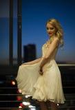 都市阳台的美丽的白肤金发的妇女 库存照片