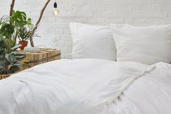 都市顶楼卧室白色床单和创造性的nighstand与植物 免版税库存照片
