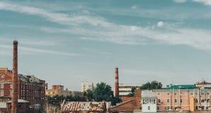都市风景、老房子和锅炉与管子反对蓝色夏天天空 库存照片