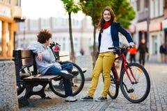 都市骑自行车-十几岁和自行车在城市 库存照片