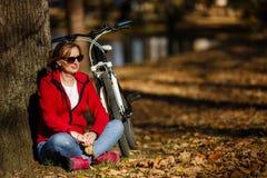 都市骑自行车-妇女骑马自行车在城市公园 库存照片
