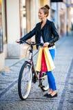 都市骑自行车-少妇和自行车在城市 免版税库存图片