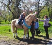 鄂木斯克,俄罗斯- 2015年5月09日:儿童的在小马的马骑术 免版税图库摄影