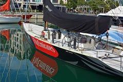 酋长管辖区队新西兰美洲杯赛游艇在高架桥港口 库存照片