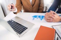 配合公司会议概念,商务伙伴与一起分析起始的财政项目的手提电脑一起使用 免版税库存照片