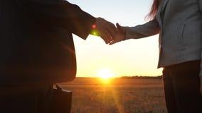 配合商人 握手在日落前的光亮的商人和女实业家 女商人通过公文包 股票录像