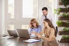 配合在办公室 小组一起研究膝上型计算机的商人在办公室 库存照片