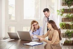配合在办公室 小组一起研究膝上型计算机的商人在办公室 图库摄影