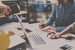 配合处理概念 年轻工友合作与新的企业项目一起使用 膝上型计算机,在木桌上的智能手机 库存照片