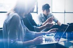 配合处理概念 年轻工友与新的起始的项目一起使用在办公室 使用现代膝上型计算机的商人  图库摄影