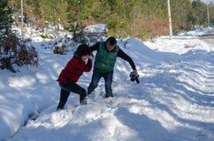 配合夫妇在雪互相帮助在冬天 图库摄影