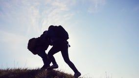 配合帮助商务旅游概念 两个徒步旅行者人和妇女游人登山人在山的上面上升 影视素材