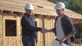 配合握手 修建建筑师慢动作录影的概念大厦 在盔甲的两个人建造者握手 股票视频