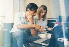 配合概念 年轻商人与新的起始的项目一起使用 拿着智能手机手中和人的妇女 免版税库存照片