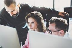 配合概念 年轻工友与新的事务一起使用在现代办公室射出 小组三个人分析数据 免版税库存图片