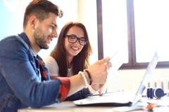 配合概念 年轻创造性的工友与新的起始的项目一起使用在现代办公室 组人三 图库摄影