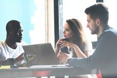 配合概念 年轻创造性的工友与新的起始的项目一起使用在现代办公室 组人三 库存图片