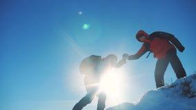 配合游人冬天雪商务旅游旅行借一个帮手 有远足的背包的两个人互相帮助 股票视频