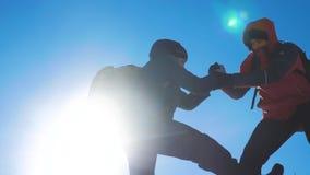 配合游人冬天雪商务旅游旅行借一个帮手 有远足的背包的两个人互相帮助 股票录像