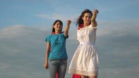 配合超级英雄 超级英雄红色斗篷的两个女孩站立反对天空蔚蓝,风膨胀斗篷 ?? 股票录像