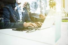 配合过程,两个年轻商人的图象使用膝上型计算机的在 库存照片