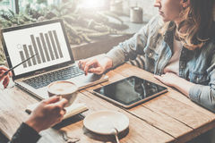配合,两个年轻人在网上工作的女商人坐在桌,饮用的咖啡上和 免版税库存照片