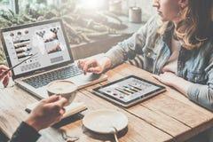 配合,两个年轻人在网上工作的女商人坐在桌,饮用的咖啡上和 库存图片