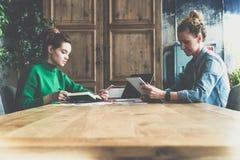 配合,在网上工作两个年轻的女商人坐在桌上和 库存照片