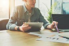 配合,群策群力 女实业家坐在桌上的和举行压片计算机,当显示在图的笔在桌上时 免版税图库摄影
