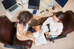 配合 两个年轻女商人谈论经营计划 库存图片