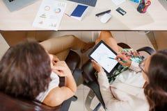 配合 两个年轻女商人谈论经营计划 免版税库存图片