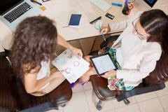 配合 两个年轻女商人谈论经营计划 免版税图库摄影