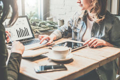 配合 两个年轻人坐在咖啡店,看看的桌上的女商人在膝上型计算机屏幕上的图和开发经营计划 库存照片