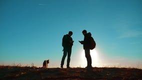 配合 两条游人徒步旅行者人和狗与背包在日落去远足旅行 慢动作录影 智能手机 股票录像