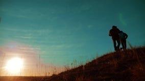配合 享受日出的两个徒步旅行者走从山和狗的上面 慢动作录影 两个徒步旅行者与 股票录像
