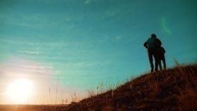 配合 享受日出的两个徒步旅行者走从山和狗的上面 慢动作录影 两个徒步旅行者生活方式 股票录像