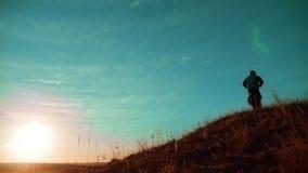 配合 享受日出的两个徒步旅行者走从山和狗的上面 慢动作录影 两个生活方式徒步旅行者 影视素材