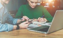配合 坐在办公室和工作的书桌的两个年轻女商人 在桌上是膝上型计算机和纸图 图库摄影