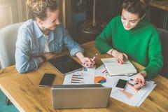 配合 坐在办公室的两个微笑的年轻女商人在桌和工作上 库存图片