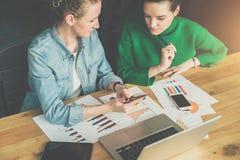 配合 坐在桌上的两个年轻女商人 女孩显示关于智能手机屏幕的同事信息 免版税库存图片