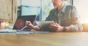 配合 女实业家坐在桌上的和举行压片计算机,当显示在图的笔在桌上时 图库摄影