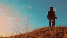 配合 有背包的两个游人徒步旅行者人在日落去远足旅行 徒步旅行者冒险生活方式,并且狗去 股票录像