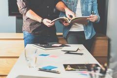 配合 年轻站立在桌和神色上的女商人和商人在目录里 免版税库存照片