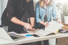 配合 站立近的桌和神色在目录信息的商人和女实业家 库存图片