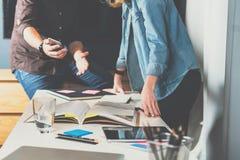 配合 站立近的桌的商人和女实业家 在书桌上是膝上型计算机、片剂个人计算机、笔记本和编目 库存照片