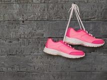 配对桃红色垂悬由在木墙壁上的鞋带的妇女的跑鞋 免版税库存图片