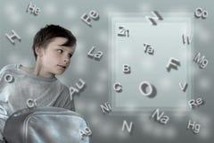 配方 有学校背包的男孩在桌Mendeleev背景  库存照片