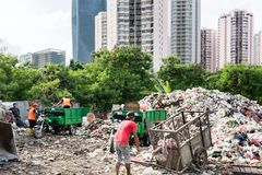配置废料和垃圾的人们在掩埋场 库存照片