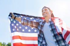 配齐快乐地微笑的爱国者,当拿着美国国旗时 免版税库存图片