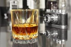 酒、科涅克白兰地、白兰地酒或者whiscy玻璃在镜子桌上 在一台酒吧和葡萄酒老照相机的瓶在背景 免版税库存图片